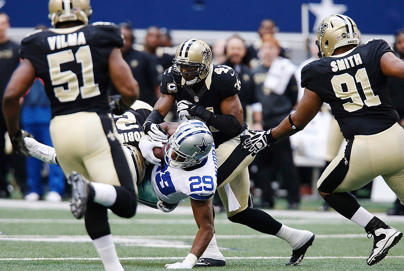 . Dallas Cowboys running back DeMarco Murray (29) is taken down by New Orleans Saints cornerback Patrick Robinson (21) and strong safety Roman Harper (41) as Saints\' Will Smith (91) and Jonathan Vilma (51) move in during the second half of an NFL football game on Sunday, Dec. 23, 2012, in Arlington, Texas. (AP Photo/Sharon Ellman)