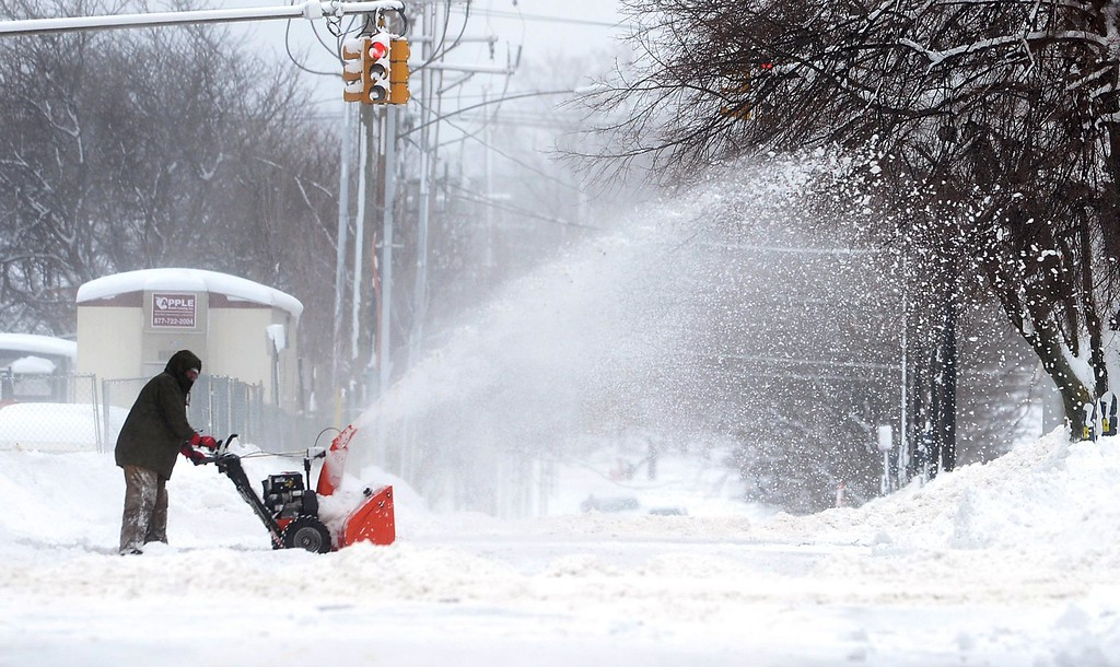 . A man clears snow on Tuesday, Dec. 26, 2017, in Erie, Pa. The National Weather Service office in Cleveland says Monday\'s storm brought 34 inches of snow, an all-time daily snowfall record for Erie. Another 19 inches fell before dawn Tuesday, making the greatest two-day total in commonwealth history. (Greg Wohlford/Erie Times-News via AP)