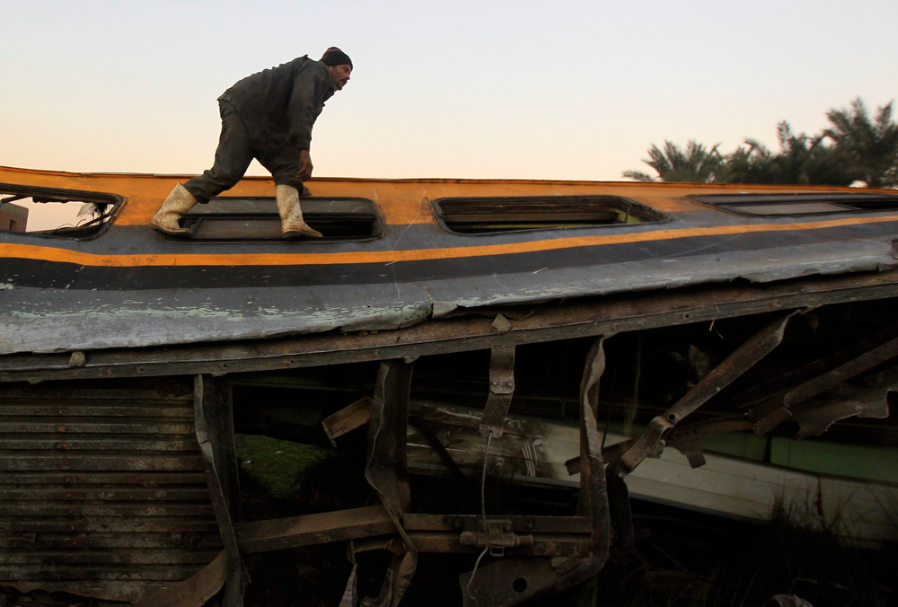 . A man inspects the wreckage of a military train crash in the Giza neighbourhood of Badrashin, about 40 km (25 miles) west of Cairo, January 15, 2013. A military train carrying young recruits to an army camp derailed in a Cairo suburb on Tuesday, killing 19 people and injuring 107, Egypt\'s health ministry spokesman said.  REUTERS/Mohamed Abd El Ghany