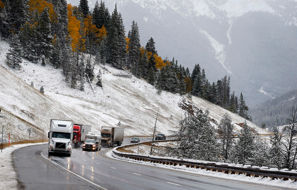 . Trucks ascend Vail Pass along I-70 after overnight snow fell in the mountains of Colorado. Friday Oct. 4, 2013. Powerful storms moved into the Midwest on Friday due to a cold weather system gaining strength as it traveled east from Colorado and Wyoming. (AP Photo/Brennan Linsley)