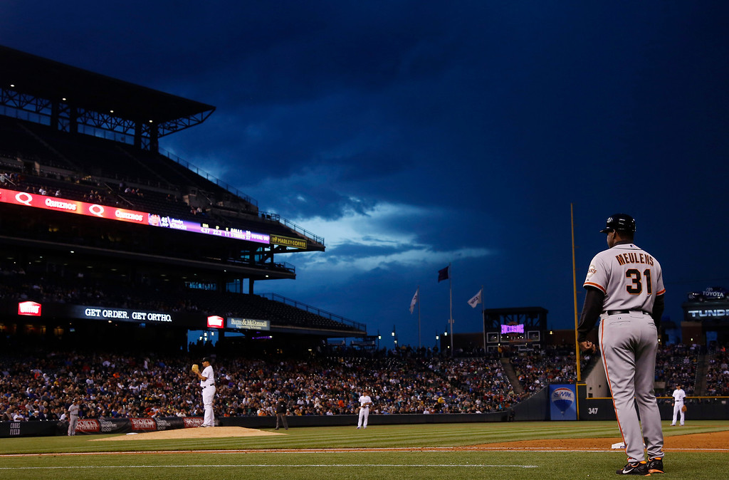 . San Francisco Giants first base coach Hensley Meulens, right, watches as clouds approach Coors Field in the sixth inning as the Colorado Rockies faced the Giants in a baseball game in Denver on Wednesday, May 21, 2014. (AP Photo/David Zalubowski)