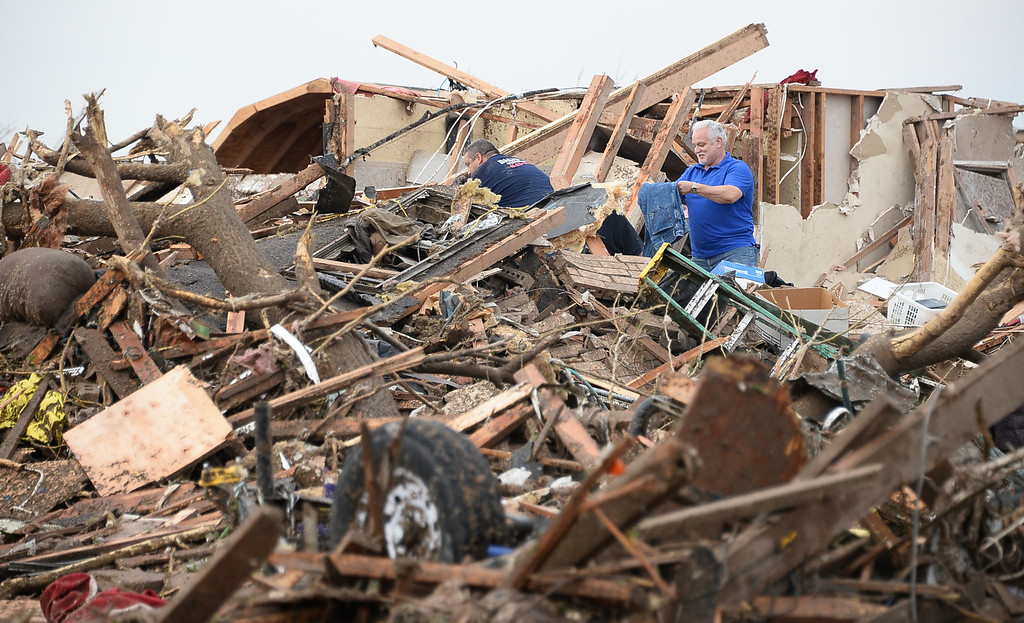 . Local Neighbors look through the mangeld mess of homes among the destroyed buildings and overturned cars. Photo by Gene Blevins/LA Daily News