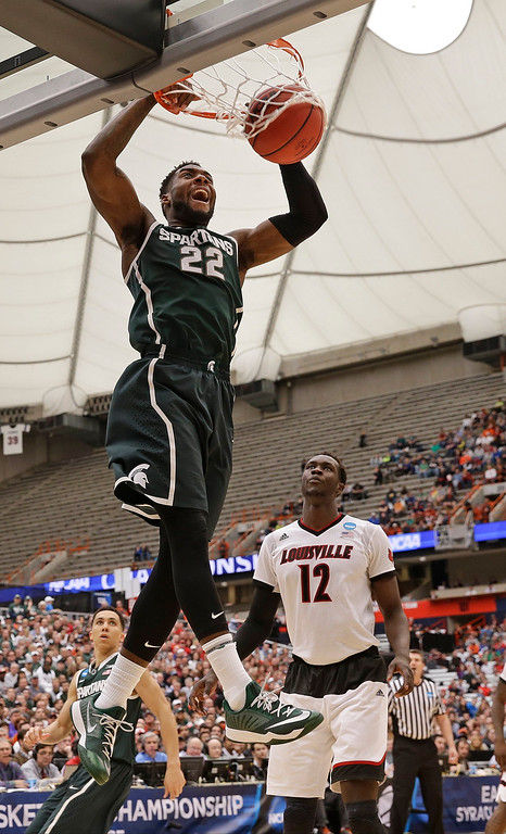 . Michigan State\'s Branden Dawson (22) dunks the ball in front of Louisville\'s Mangok Mathiang (12), of Australia, during the second half of a regional final in the NCAA men\'s college basketball tournament Sunday, March 29, 2015, in Syracuse, N.Y. (AP Photo/Seth Wenig)