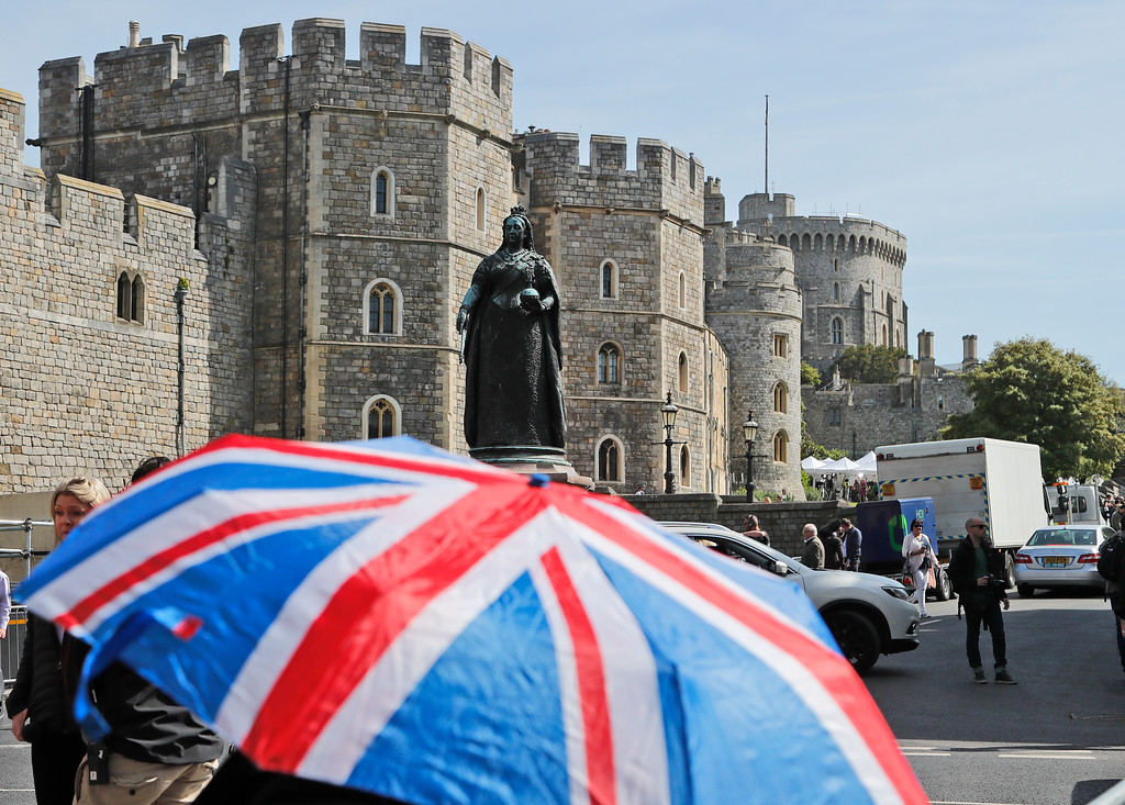 . A Union Jack umbrella covers fans from the sun in front of Windsor Castle in Windsor, Friday, May 18, 2018. Preparations are being made in the town ahead of the wedding of Britain\'s Prince Harry and Meghan Markle that will take place in Windsor on Saturday May 19.(AP Photo/Frank Augstein)