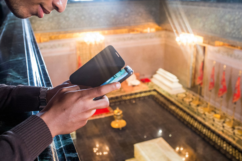 Young man checking his smartphone inside Mohammed V's mausoleum, Rabat, Morocco. The Mausoleum of Mohammed V is a historical building located on the opposite side of the Hassan Tower on the Yacoub al-Mansour esplanade in Rabat, Morocco. It contains the tombs of the Moroccan king and his two sons, late King Hassan II and Prince Abdallah. The building is considered a masterpiece of modern Alaouite dynasty architecture, with its white silhouette, topped by a typical green tiled roof, green being the color of Islam. A reader of the Koran is often present, having his assigned seat. Its construction was completed in 1971. Hassan II was buried there following his death in 1999