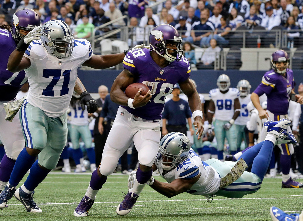 . Minnesota Vikings running back Adrian Peterson (28) looks for running room under pressure from Dallas Cowboys\' Everette Brown (71) and Barry Church (42) in the first half of an NFL football game, Sunday, Nov. 3, 2013, in Arlington, Texas. (AP Photo/Nam Y. Huh)