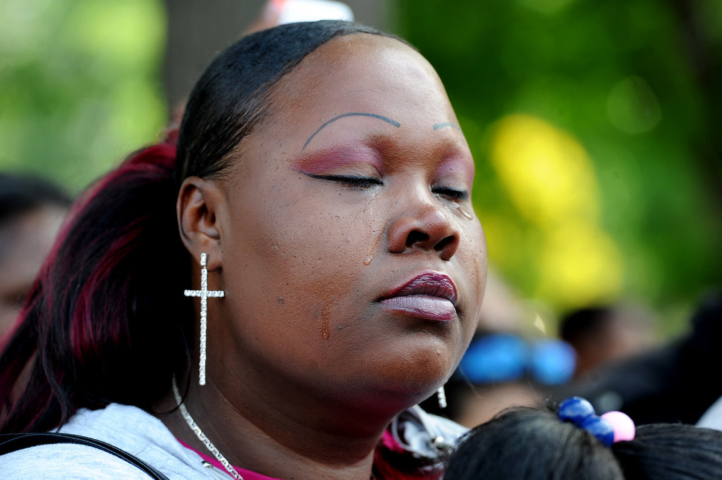 """. Tamesah Morris shed tears during the rally in City Park in Denver, CO on July 14, 2013.  Members of the African American community turned out for a rally  to show their disappointment in the acquittal of George Zimmerman in the murder trail of Trayvon Martin on July 14, 2013. Zimmerman is the Florida man who shot and killed Trayvon Martin. \""""We will not erase the conversation of race,\"""" said Jeff Fard, founder of Brother Jeff\'s Cultural Center in the Five Points neighborhood. \""""Don\'t be afraid to say if Trayvon Martin was a white man he would be alive today.\""""  Photo by Helen H. Richardson/The Denver Post)"""