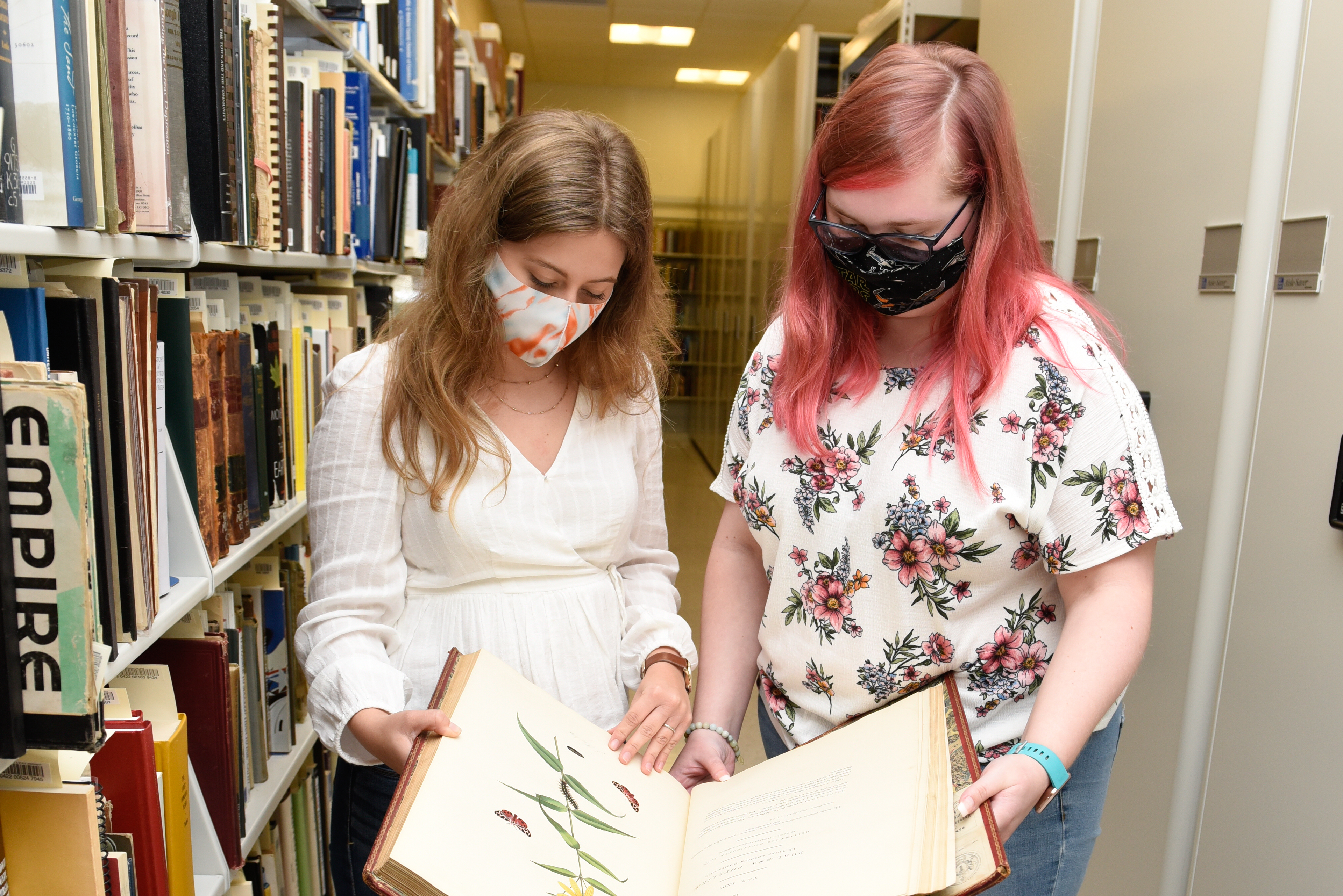 Student assistants in Special Collections at the Russell Library examine a botanical illustration.