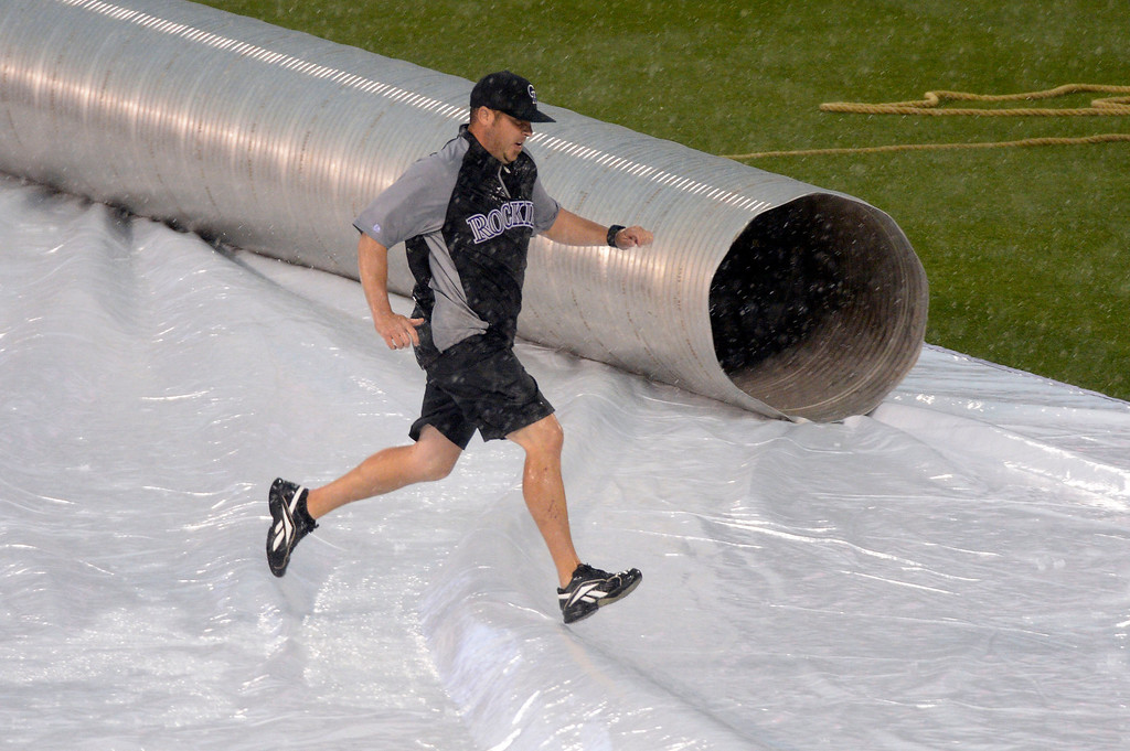 . DENVER, CO - MAY 22: Grounds crew Jason Garner rushes to pull the tarp tight during a second rain delay during the Colorado Rockies San Francisco Giants game May 22, 2014 at Coors Field. (Photo by John Leyba/The Denver Post)