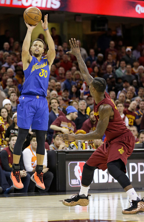 . Golden State Warriors\' Stephen Curry (30) shoots over Cleveland Cavaliers\' Iman Shumpert (4) in the second half of an NBA basketball game, Sunday, Dec. 25, 2016, in Cleveland. (AP Photo/Tony Dejak)