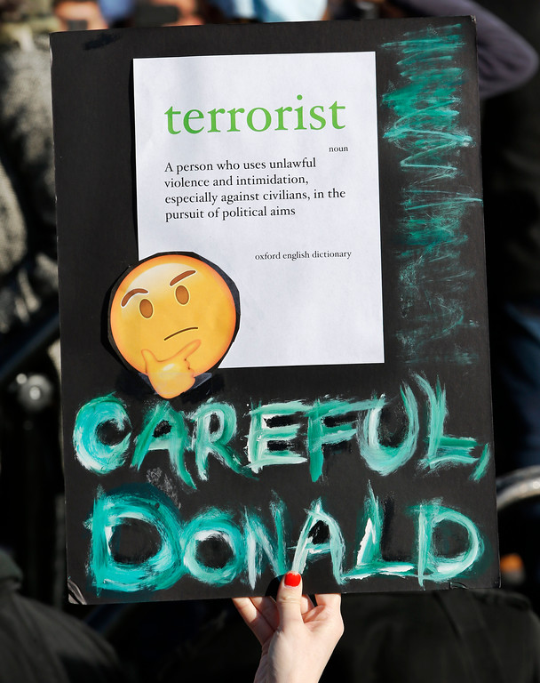 . A woman holds up a sign with the definition of the word terrorist on it as she and others participate in an immigrants\' rights\' rally Sunday, Jan. 29, 2017, in New York\'s Battery Park. President Donald Trump\'s immigration order sowed more chaos and outrage across the country Sunday, with travelers detained at airports, panicked families searching for relatives while protesters registered opposition to the sweeping measure that was blocked by several federal courts. (AP Photo/Kathy Willens)