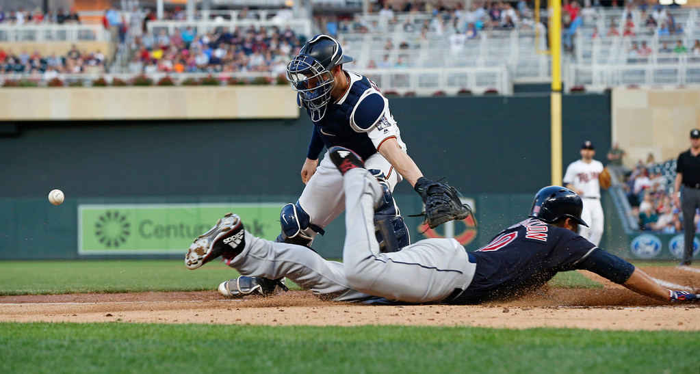 . Minnesota Twins catcher Mitch Garver, left, reaches to make a tag, minus the ball as Cleveland Indians\' Edwin Encarnacion scores on a hit by Melky Cabrera during the fourth inning of a baseball game Thursday, May 31, 2018, in Minneapolis. (AP Photo/Jim Mone)