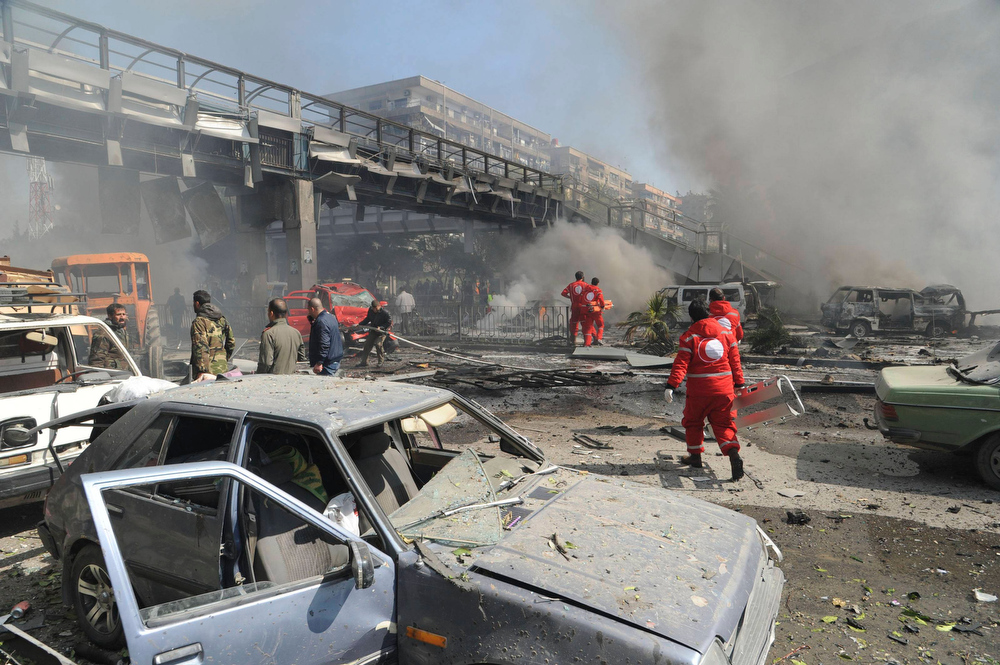 Description of . People walk near damaged cars after an explosion at central Damascus February 21, 2013, in this handout photograph released by Syria's national news agency SANA. The big explosion shook the central Damascus district of Mazraa on Thursday, residents said, and Syrian state media blamed what it said was a suicide bombing on
