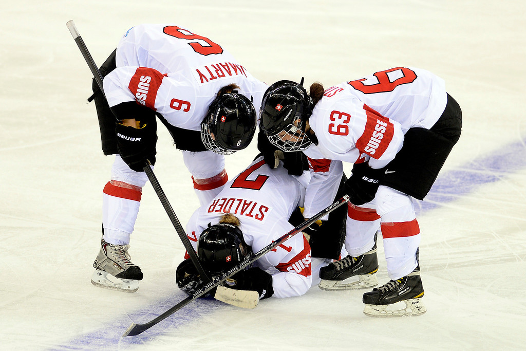 . Lara Stalder (7) of the Switzerland lays on the ice after getting checked into the boards by Kendall Coyne (26) of the U.S.A. as teammates Julia Marty (6) and Anja Stiefel (63) during the third period of the United States\' 9-0 win at the Shayba Arena. Sochi 2014 Winter Olympics on Monday, February 10, 2014. (Photo by AAron Ontiveroz/The Denver Post)