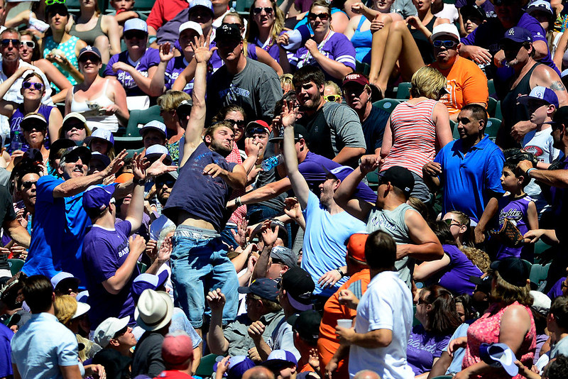 . A fan leaps for a foul ball during the third inning between the San Diego Padres and the Colorado Rockies in Denver. The Colorado Rockies hosted the San Diego Padres at Coors Field on Sunday, June 9, 2013. (Photo by AAron Ontiveroz/The Denver Post)
