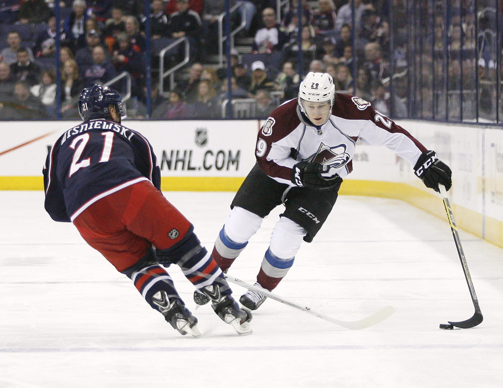. Columbus Blue Jackets\' David Wisniewski (21) tries to slow down Colorado Avalanche\'s Nathan MacKinnon (29) during the first period of an NHL hockey game, Tuesday, April 1, 2014, in Columbus, Ohio. (AP Photo/Mike Munden)