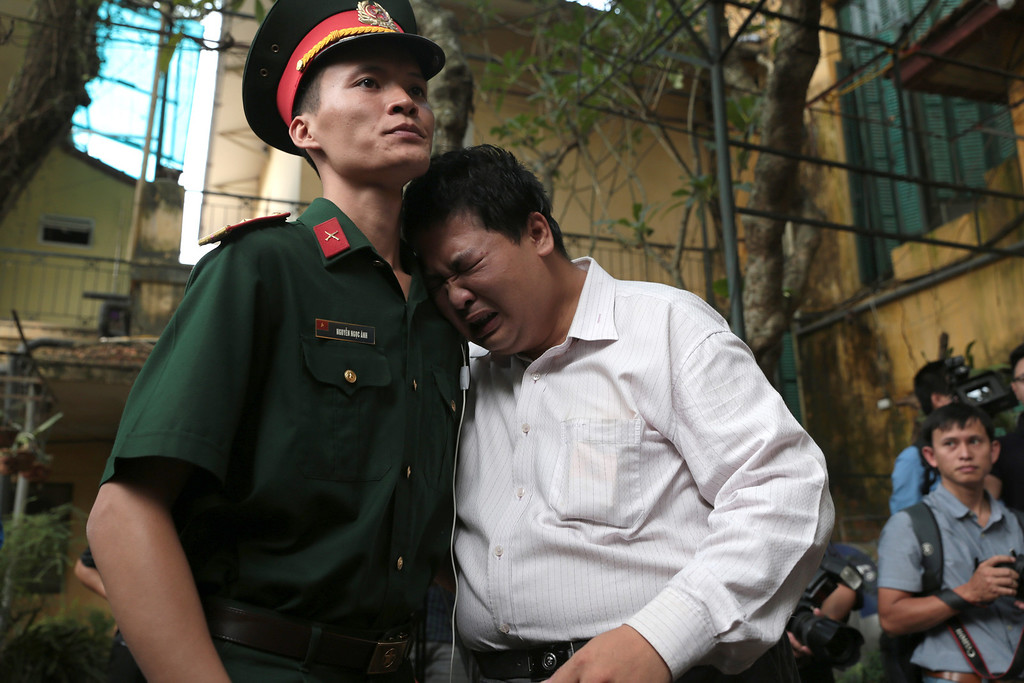 . A man cries on a military officer in the garden of the house of the late Gen. Vo Nguyen Giap in Hanoi, Vietnam after paying homage to Giap on Sunday, Oct. 6, 2013. The brilliant and ruthless commander who led the outgunned Vietnamese to victory first over the French and then the Americans, died Friday, Oct. 4. The last of the country\'s old-guard revolutionaries was 102. (AP Photo/Na Son Nguyen).