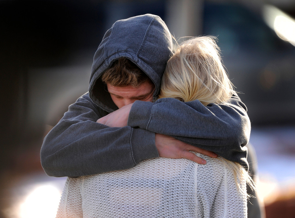 . CENTENNIAL, CO. - DECEMBER 13: Students embraced outside Arapahoe High School Friday afternoon. They would have to wait hours to be reunited with their parents. Parents waited to be reunited with their children outside Arapahoe High School Friday afternoon, December 13, 2013. A shooting inside the school sent hundreds of students rushing for safety. Photo By Karl Gehring/The Denver Post