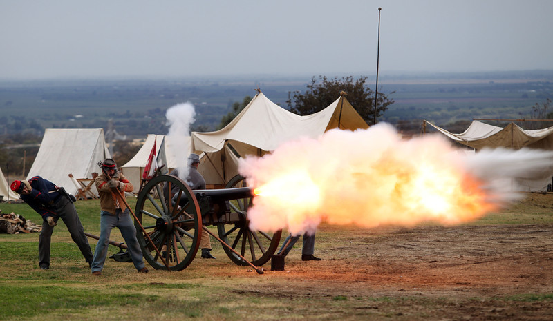 """South Confederates (seen) fire a cannon to engage the North Union in a """"Battle of Tuscan Ridge"""" Civil War re-enactment at Tuscan Ridge Golf Course Saturday, October 23, 2010 in Chico, Calif. (Jason Halley/Chico Enterprise-Record)"""