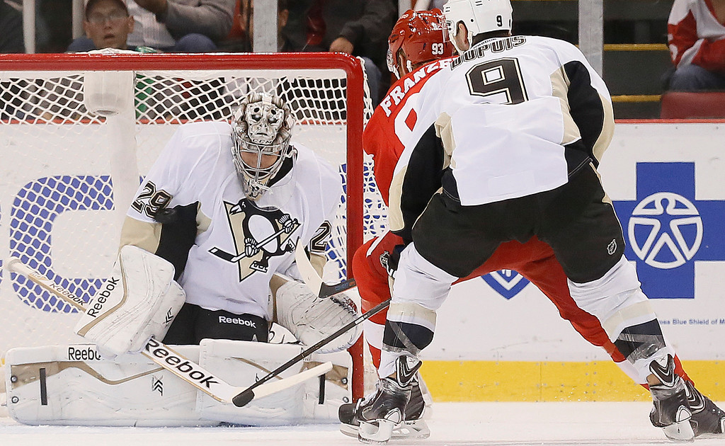 . Pittsburgh Penguins goalie Marc-Andre Fleury (29) stops a Detroit Red Wings\' Johan Franzen (93), of Sweden, shot as Pascal Dupuis (9) defends in the first period of a NHL preseason hockey game in Detroit Wednesday, Oct. 1, 2014. (AP Photo/Paul Sancya)