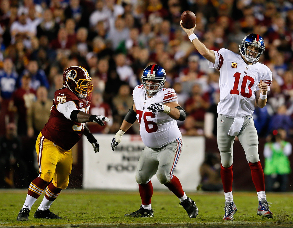 . LANDOVER, MD - DECEMBER 03:  Quarterback  Eli Manning #10 of the New York Giants throws the ball as teammate Chris Snee #76 blocks Barry Cofield #96 of the Washington Redskins in the first half at FedExField on December 3, 2012 in Landover, Maryland.  (Photo by Rob Carr/Getty Images)