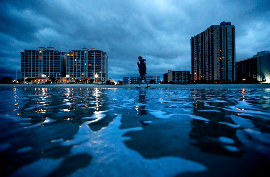 ". Russ Lewis looks for shells along the beach as Hurricane Florence approaches Myrtle Beach, S.C., Friday, Sept. 14, 2018. ""We might get lucky we might not we\'ll find out,\"" said Lewis of the storm. (AP Photo/David Goldman)"