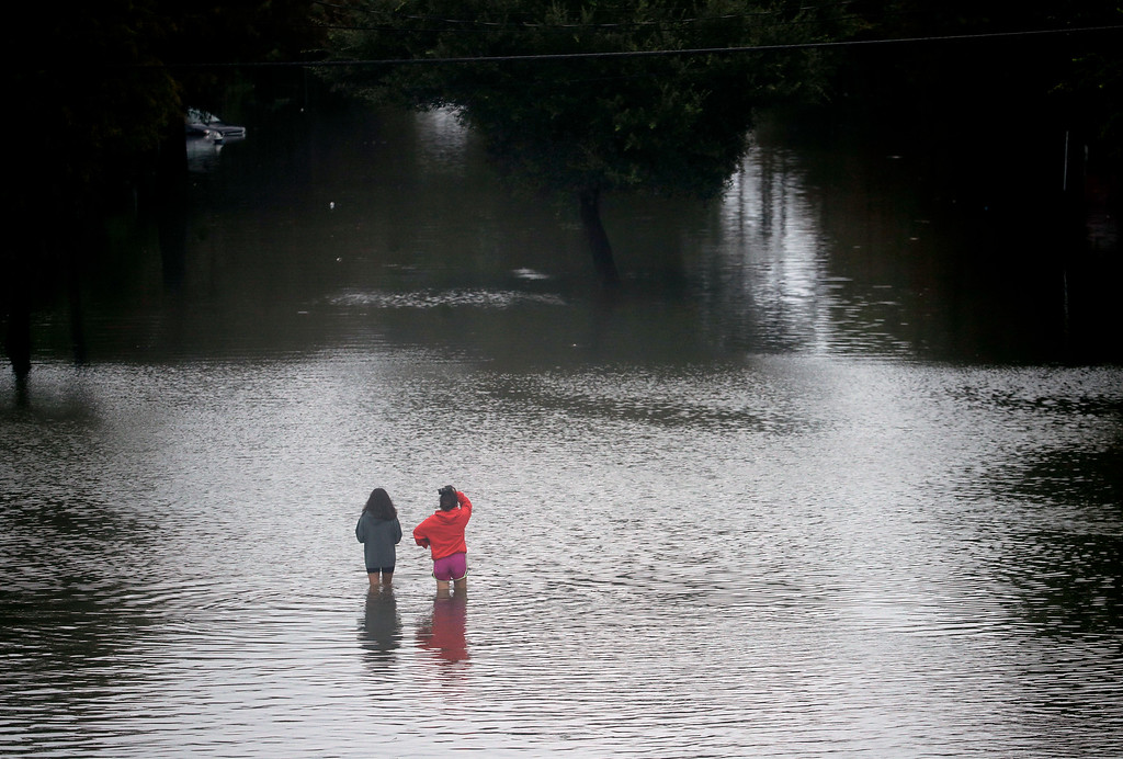 . People walk through floodwaters from Tropical Storm Harvey on Sunday, Aug. 27, 2017, in Houston. (AP Photo/Charlie Riedel)