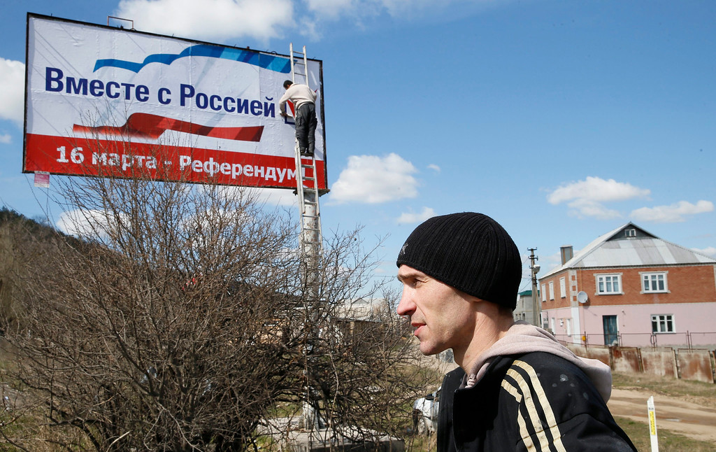 . A worker puts up a poster that reads \'Together with Russia, March 16 - referendum\', outside Simferopol, Ukraine, 13 March 2014. Crimea\'s secessionist authorities said on 12 March that they have partially closed the region\'s airspace to \'keep out provocateurs\', in the run-up to the March 16 referendum about joining Russia.  EPA/YURI KOCHETKOV