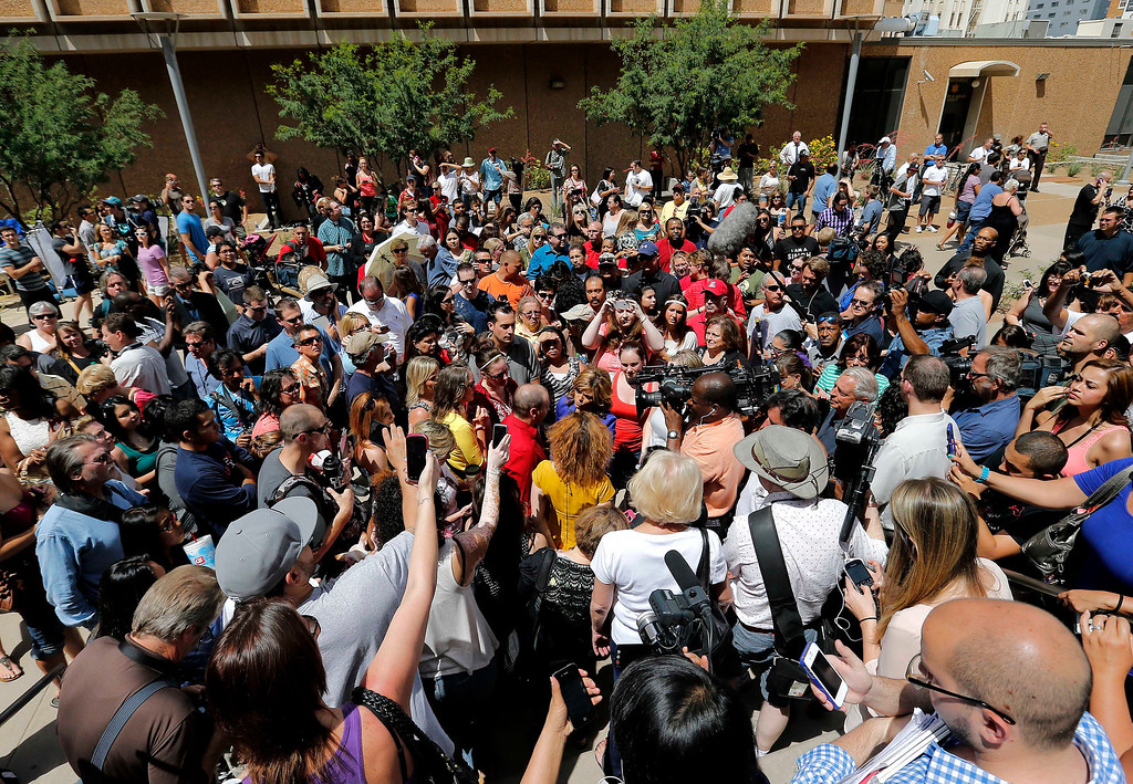 . Spectators react in Phoenix, Wednesday, May 8, 2013 to a guilty verdict in the trial of Jodi Arias, a waitress and aspiring photographer charged with killing her boyfriend, Travis Alexander, in Arizona in 2008. The four month trial included graphic details of their sexual escapades and photos of Alexander just after his death. (AP Photo/Matt York)