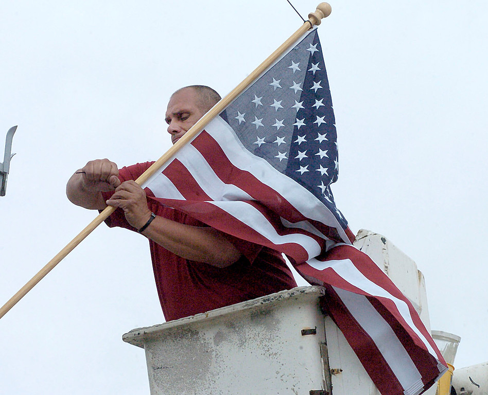 . Wilkes-Barre DPW employee Dave Lewis installs an American flag on the Market Street Bridge, Thursday May 23, 2013 in Wilkes-Barre, Pa. in conjunction with veterans organizations for Memorial Day weekend. (AP Photo/The Citizens\' Voice, Mark Moran)  MANDATORY CREDIT