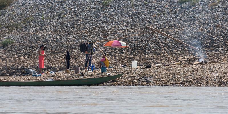 People and boat along shoreline, River Mekong, Laos