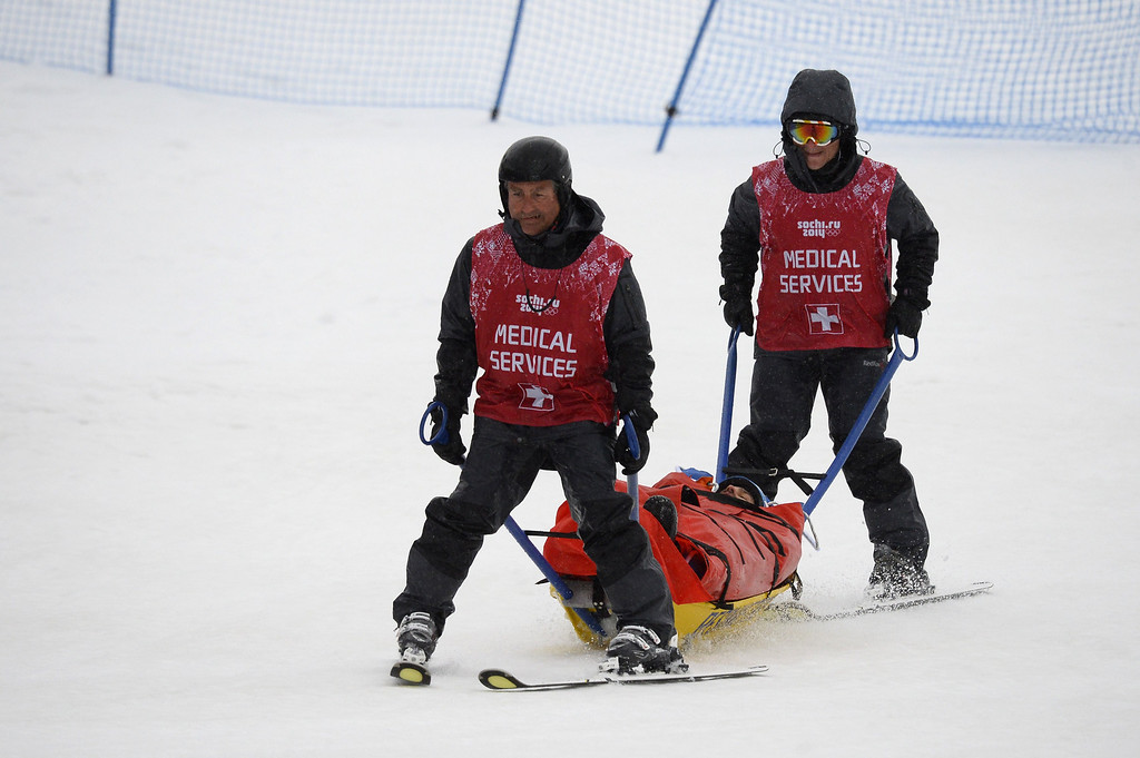 . Italy\'s Omar Visintin is taken off the course after crashing in Heat 14 of the Men\'s Snowboard Cross Final at the Rosa Khutor Extreme Park during the Sochi Winter Olympics on February 18, 2014.  AFP PHOTO / LIONEL BONAVENTURE/AFP/Getty Images