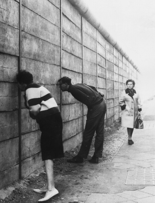 . West Berliners peering through the Berlin Wall into the Eastern sector near Check Point Charlie. The newly erected wall has no barbed wire only tubes which make it difficult to gain a handhold should anyone try to climb over.   (Photo by Keystone/Getty Images)