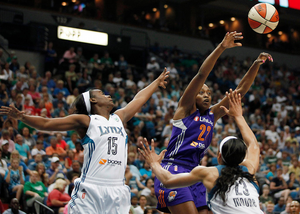 . Phoenix Mercury forward Charde Houston (22) passes the ball away from Minnesota Lynx guard Ta\'Shauna Rodgers and forward Maya Moore (23) in the second half.(AP Photo/Stacy Bengs)