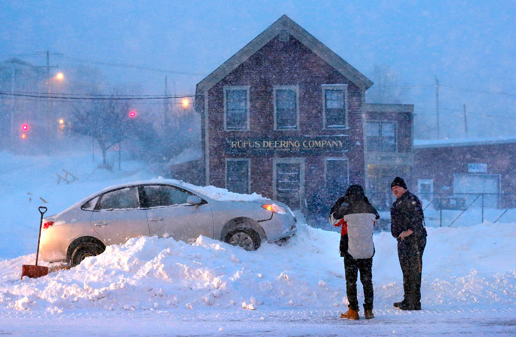 . A police officer questions the driver an occupant of a car that ended up on top of a tall snowbank in the middle of Commercial Street during a blizzard, Tuesday, Jan 27, 2015, in Portland, Maine. Although there is no driving ban in Maine, most motorists stayed off the roads on Tuesday. The storm is expected to dump up to two feet of snow. (AP Photo/Robert F. Bukaty)