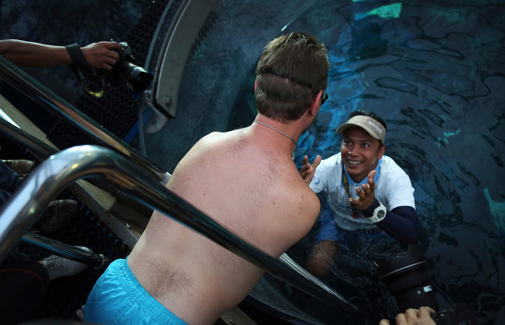 """. Nick Vujicic surveys the acrylic enclosure submerged into a shark enclosure to keep him safe while diving among the sharks, Thursday, Sept. 5, 2013, in Singapore. Vujicic, a Serbian Australian evangelist and motivational speaker born with tetra-amelia syndrome, a rare disorder characterized by the absence of all four limbs, is in the city-state to give a motivational talk and was visiting  \""""The Shark Encounter at Marine Life Park\"""" at one of Singapore\'s main tourist attractions in Resorts World Sentosa. (AP Photo/Wong Maye-E)"""