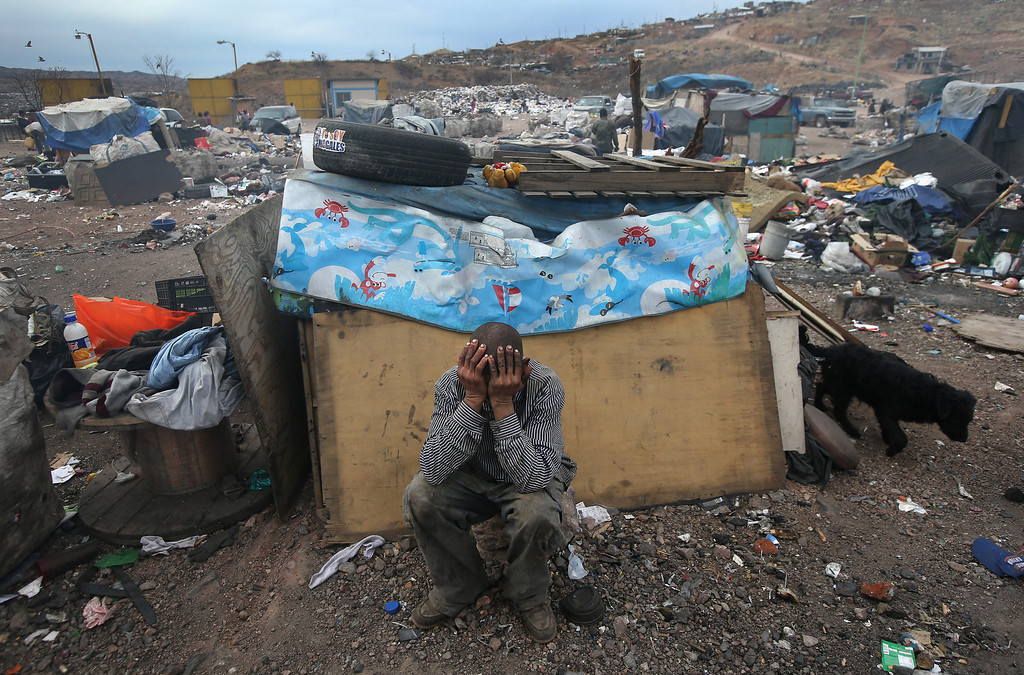. NOGALES, MEXICO - MARCH 05:  Former undocumented immigrant Arturo Santana sits in front of his modest home at the Tirabichi garbage dump on March 5, 2013 in Nogales, Mexico. He said he had been living and working in Des Moines, Iowa when he was picked up and deported by U.S. Customs and Border Protection agents in 2010. He said he still has 3 children living there with their mother. About 30 families live at the landfill, searching for recyclables to sell for a living. Many have received protective gloves from the nearby non-profit Home of Hope and Peace, which plans to expand its assistance to Tirabichi residents.  (Photo by John Moore/Getty Images)