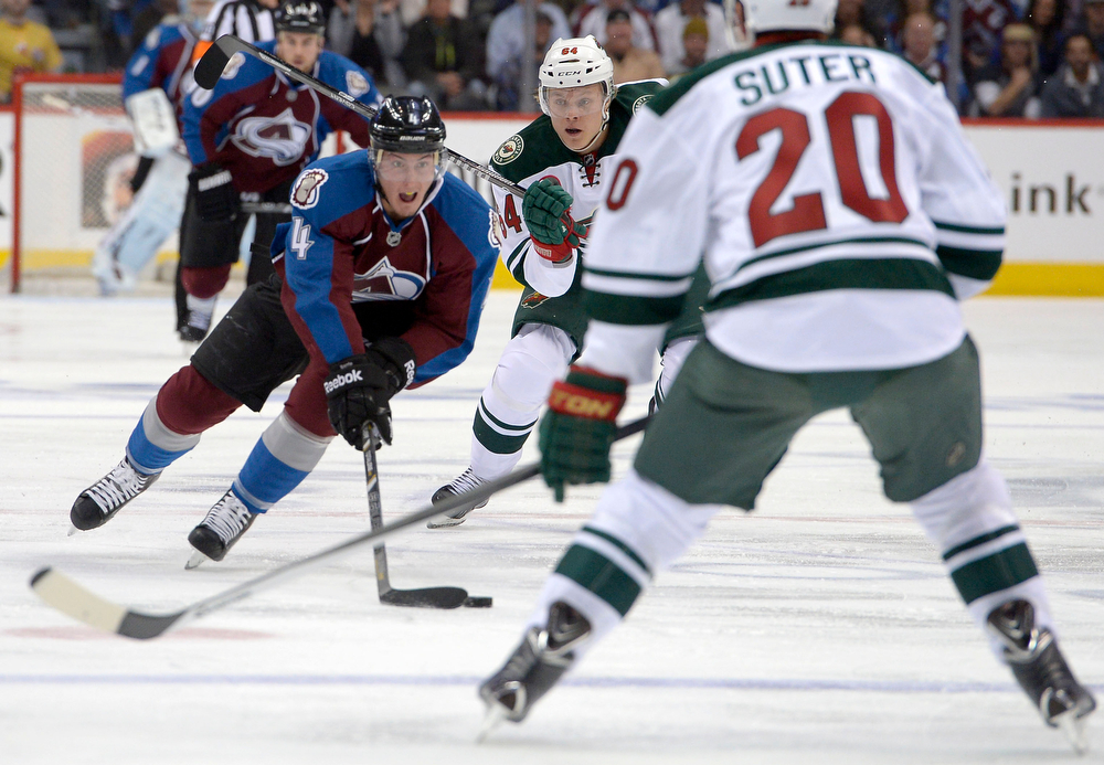 . Tyson Barrie (4) of the Colorado Avalanche brings the puck up the ice as Mikael Granlund (64) of the Minnesota Wild pursues during the first quarter of action. The Colorado Avalanche hosted the Minnesota Wild for the first playoff game at the Pepsi Center on Thursday, April 17, 2014. (Photo by John Leyba/The Denver Post)