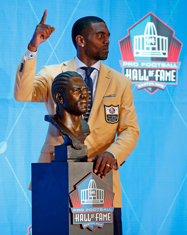 . Former NFL wide receiver Randy Moss poses with a bust of himself during inductions at the Pro Football Hall of Fame, Saturday, Aug. 4, 2018 in Canton, Ohio. (AP Photo/Ron Schwane)