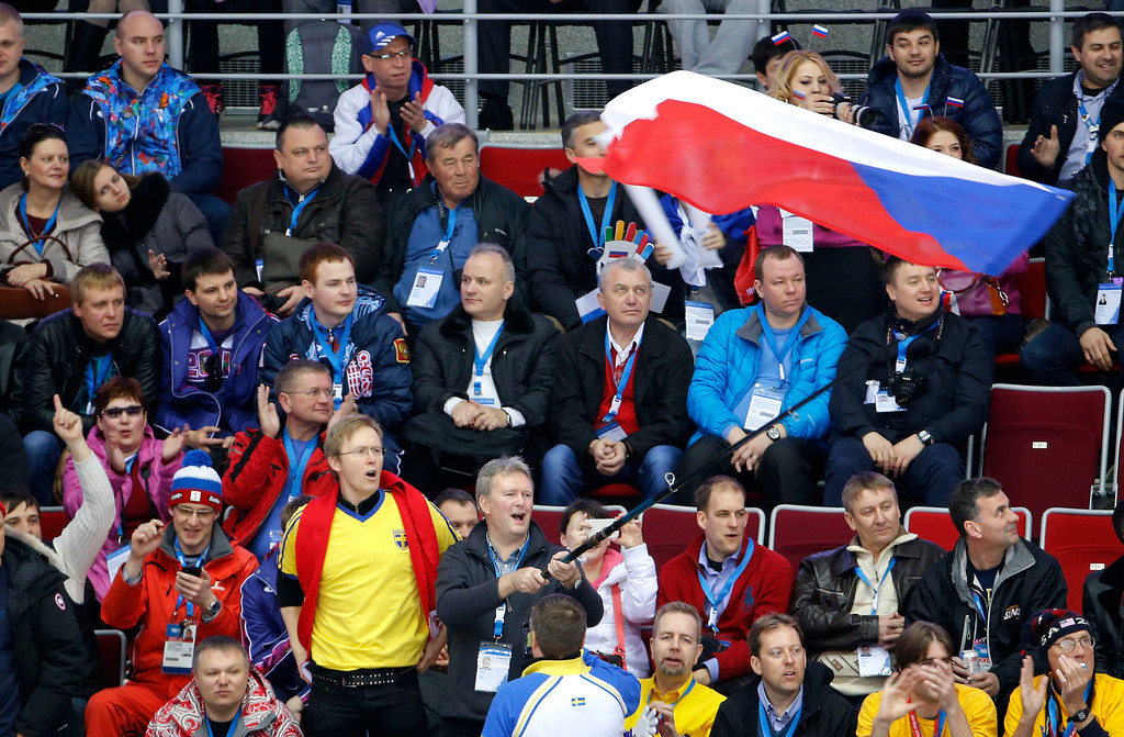 . Fans cheering for the Czech Republic wave a flag before a men\'s ice hockey game against Sweden at the 2014 Winter Olympics, Wednesday, Feb. 12, 2014, in Sochi, Russia. (AP Photo/Julio Cortez)