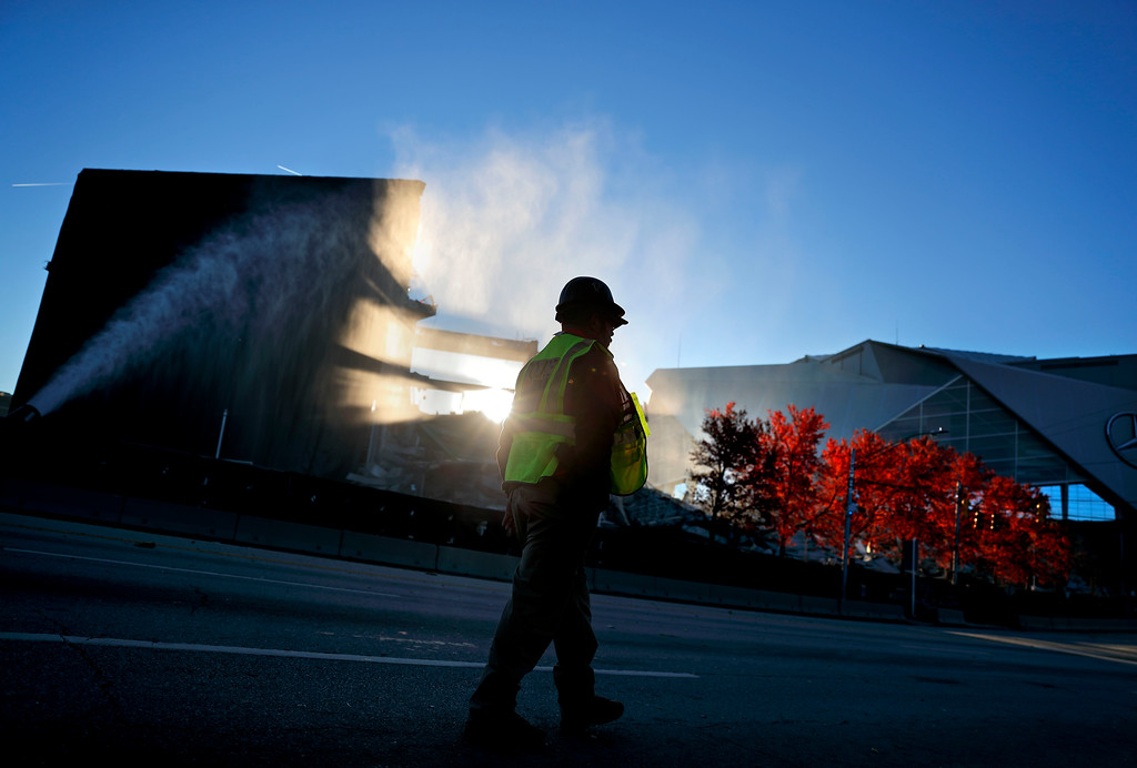 . A police officer walks past the remains of the Georgia Dome after it was is imploded next to Mercedes-Benz Stadium at right, the new home of the Atlanta Falcons, in Atlanta, Monday, Nov. 20, 2017. The dome was not only the former home of the Atlanta Falcons but also the site of two Super Bowls, 1996 Olympics Games events and NCAA basketball tournaments among other major events. (AP Photo/David Goldman)