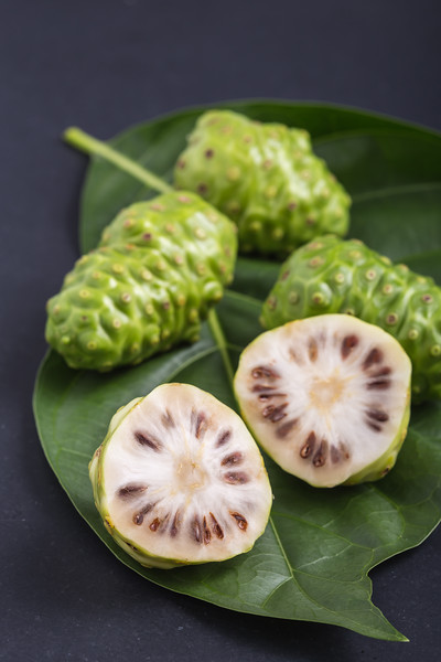 Fruit Of Great Morinda (noni) Or Morinda Citrifolia Tree And Green Leaf On Black Stone Board
