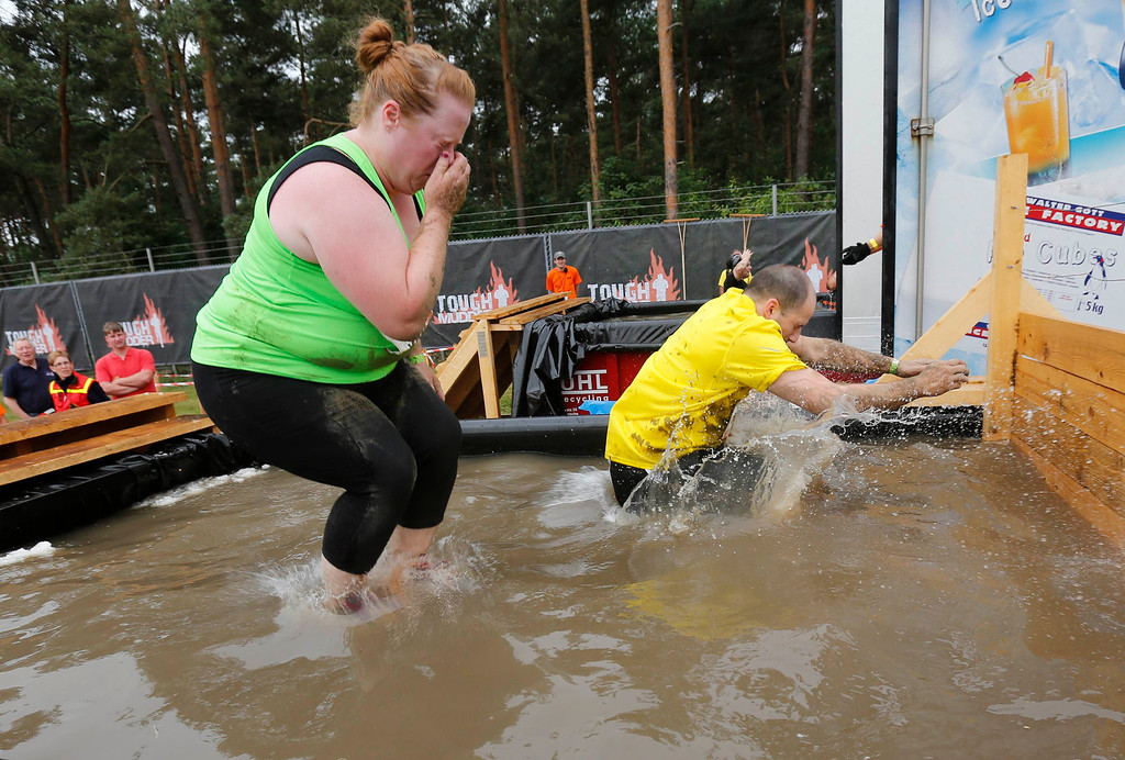 """. Heather Cozad of the United States jumps into the ice-cubes filled \""""Arctic Enema\"""" obstacle of the \""""Tough Mudder\"""" endurance event series in the Fursten Forest, a former British Army training ground near the north-western German city of Osnabrueck July 13, 2013. The hardcore but un-timed event over 16 km (10 miles) was designed by British Special Forces to test mental as well as physical strength. Some 4,000 competitors had to overcome obstacles of common human fears, such as fire, water, electricity and heights.   REUTERS/Wolfgang Rattay"""