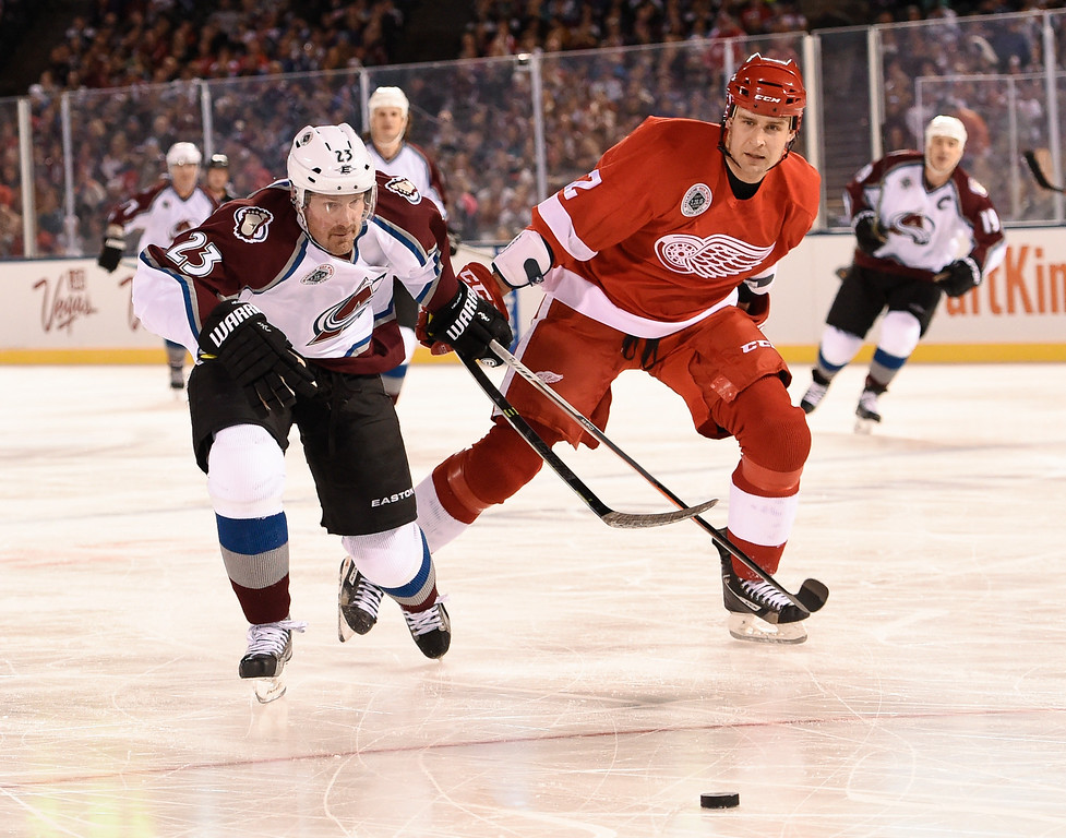 . DENVER, CO - FEBRUARY 26: Colorado Avalanche Milan Hajduk (23) and Detroit Red Wings Jiri Fischer (2) chase after the puck during the third period February 26, 2016 at Coors Field. (Photo By John Leyba/The Denver Post)