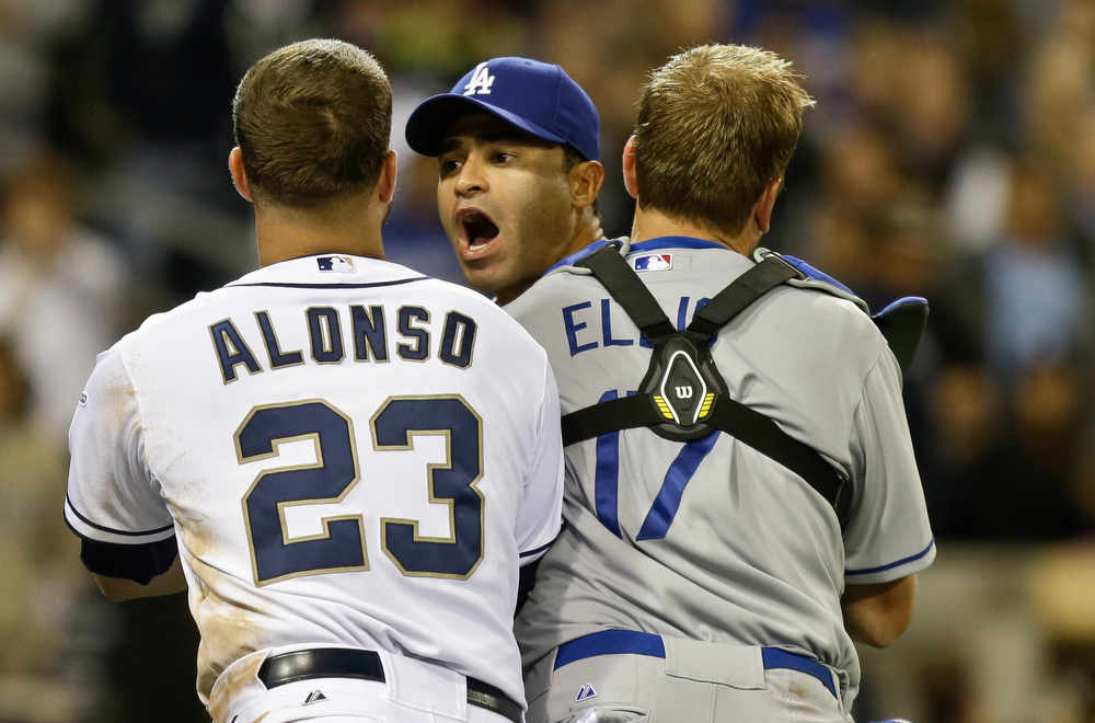 . Los Angeles Dodgers\' Jerry Hairston Jr. is restrained by A.J. Ellis and San Diego Padres\' Yonder Alonso after a braw that had subsided started up again during the sixth inning of baseball game in San Diego, Thursday, April 11, 2013. (AP Photo/Lenny Ignelzi)