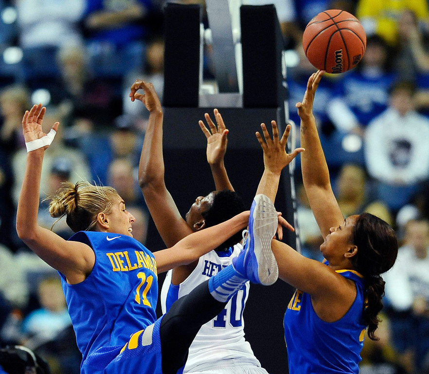 . Delaware\'s Elena Delle Donne, left, blocks a shot by Kentucky\'s Brittany Henderson, center, as Delaware\'s Jaquetta May, right, defends during the first half of a regional semifinal in the NCAA college basketball tournament in Bridgeport, Conn., Saturday, March 30, 2013. (AP Photo/Jessica Hill)