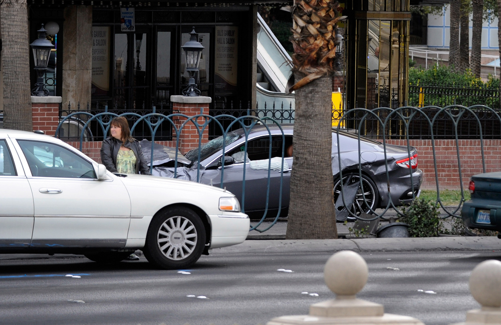 Description of . A woman stands by her vehicle near the site of what is being described as a gun battle between shooters in two vehicles along the Las Vegas Strip on February 21, 2013 in Las Vegas, Nevada. According to reports gunshots were fired between black SUV at a Maserati, causing the Maserati to crash into a taxi, that burst into flames. Five vehicles were involved in the subsequent crash with the Maserati driver and two people in the taxi being killed.  (Photo by David Becker/Getty Images)