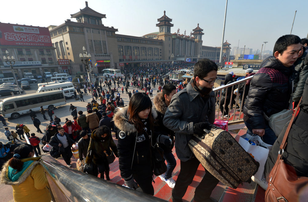 Description of . Chinese travelers arrive to board trains as the annual Lunar New Year exodus begins at Beijing train station on January 26, 2013.  The holiday also known as the Spring Festival sees tens of millions of migrant workers who provide the labour in the country\'s prosperous cities return to their villages and towns to spend time with the families left behind.    AFP PHOTO/Mark RALSTONMARK RALSTON/AFP/Getty Images