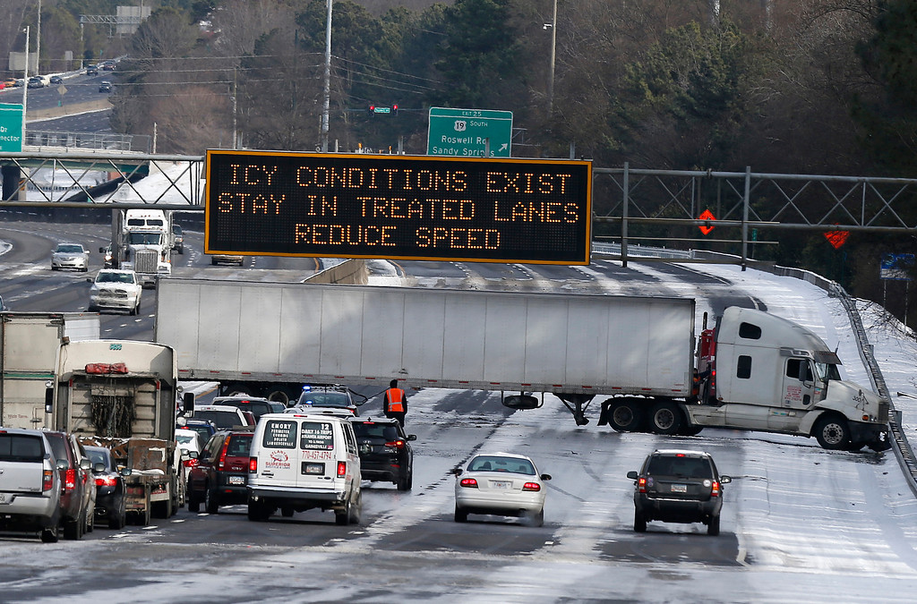 . A truck blocks all east-bound lanes of   Interstate 285 in Sandy Spring, Ga. after htting an icet patch of road. Wednesday, Jan. 29, 2014, in Atlanta.   Some interstates remained clogged by jackknifed 18-wheelers Wednesday afternoon, more than 24 hours after snow began falling on the city.  (AP Photo/John Bazemore)