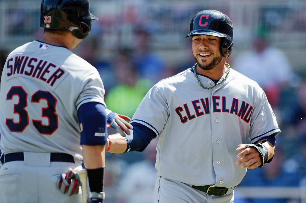 . Cleveland\'s Nick Swisher, left,  congratulates teammate Mike Aviles, who scored on a single by Jason Kipnis against the Twins during the ninth inning. (Photo by Hannah Foslien/Getty Images)